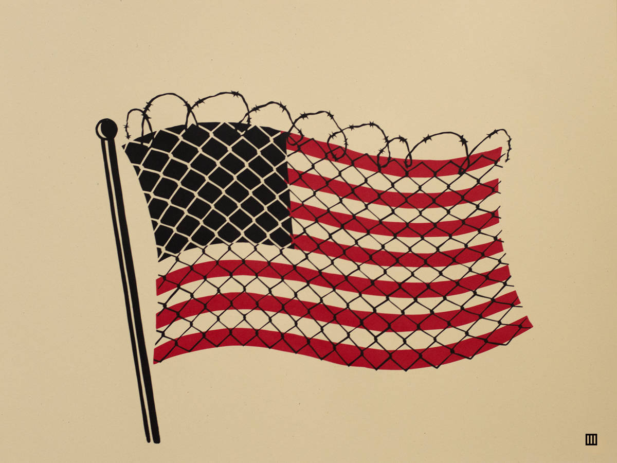 Waving American flag wrapped in chain link with razor wire across the top.