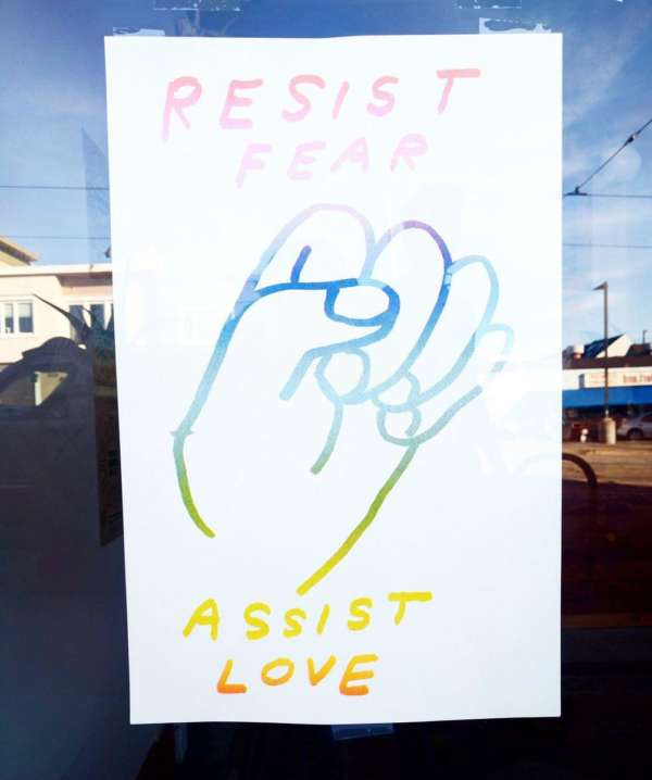 "Colorful poster hanging in a window that reads ""Resist Fear Assist Love."""