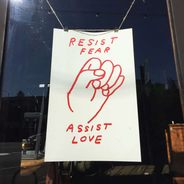 "Red ink on white paper ""Resist Fear Assist Love"" poster hangs in a window."