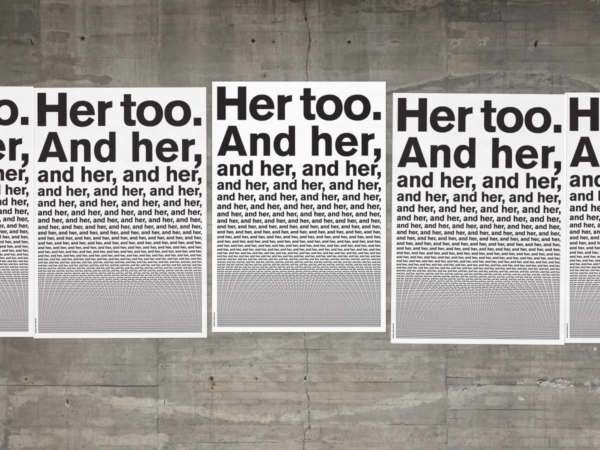 "Poster reading ""Her too. And her,"" posted to a concrete wall."