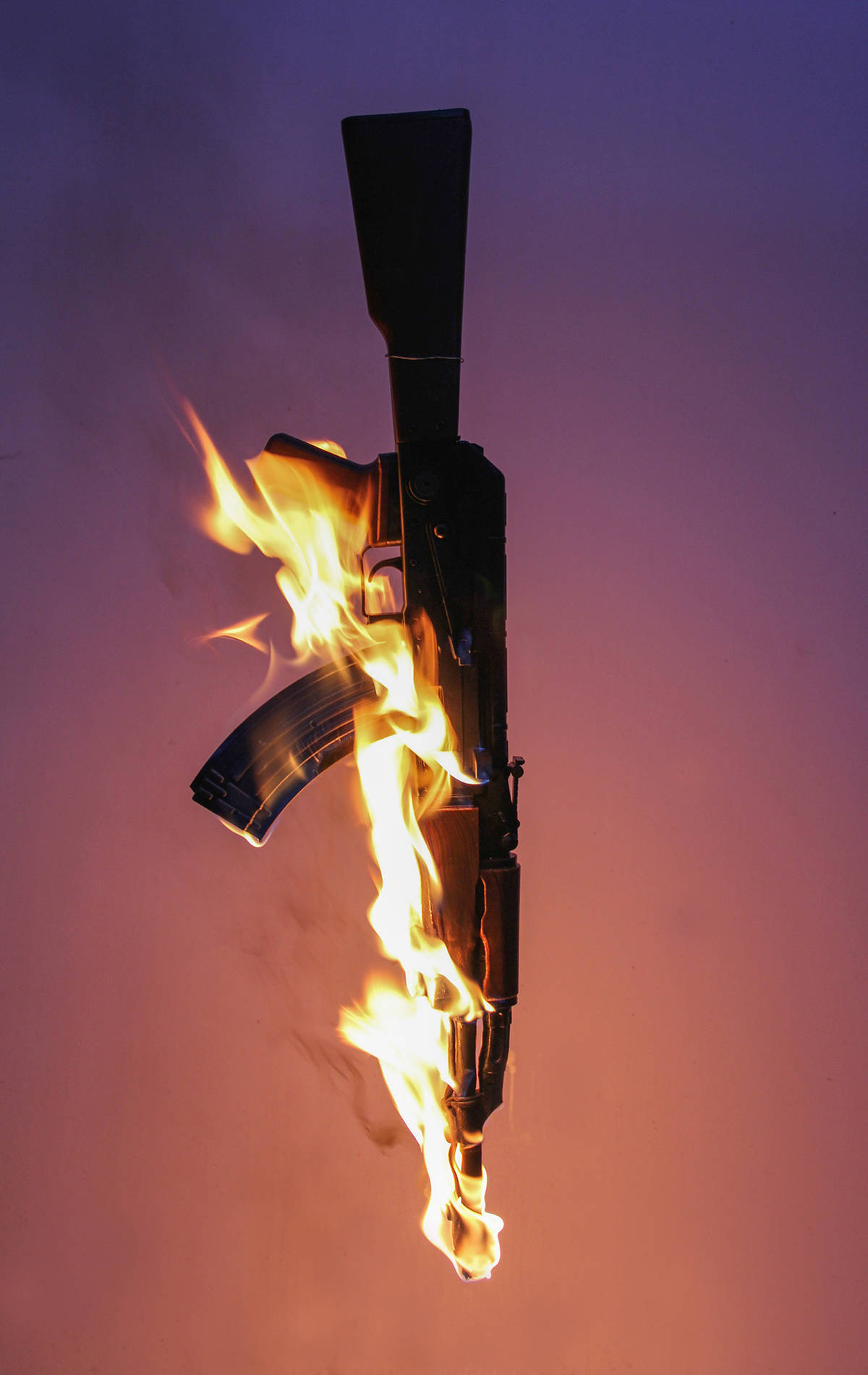 Photograph of an AK-47 machine gun set on fire against a purple and orange backdrop.