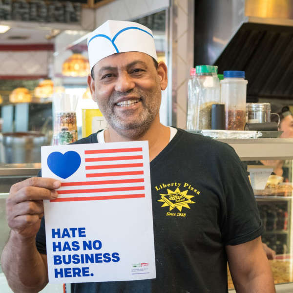 "Middle Eastern pizza chef holds up a sign that reads ""hate has no business here."""