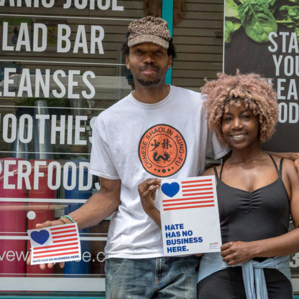 "A black man and a black woman hold up signs reading ""hate has no business here"" in front of their juice bar."
