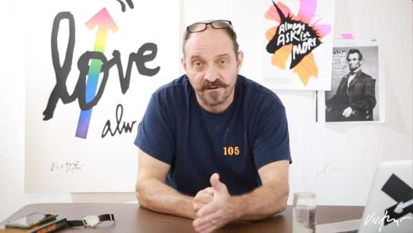 "Photo of James Victore leaning on a table in front of his ""love, always"" poster design."
