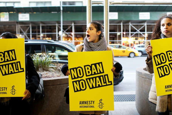 "Three women stand on the street in NYC holding posters that read ""No Ban No Wall."""