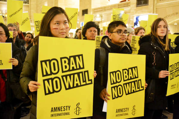 "Diverse crowd of people stand in Grand Central Station in NYC holding posters that read ""No Ban No Wall."""