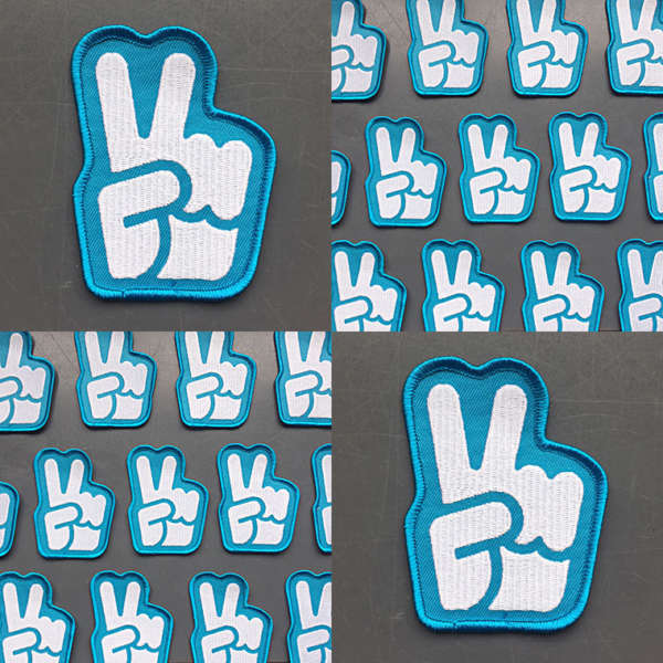 "Embroidered patches of a hand icon giving the ""peace sign."""