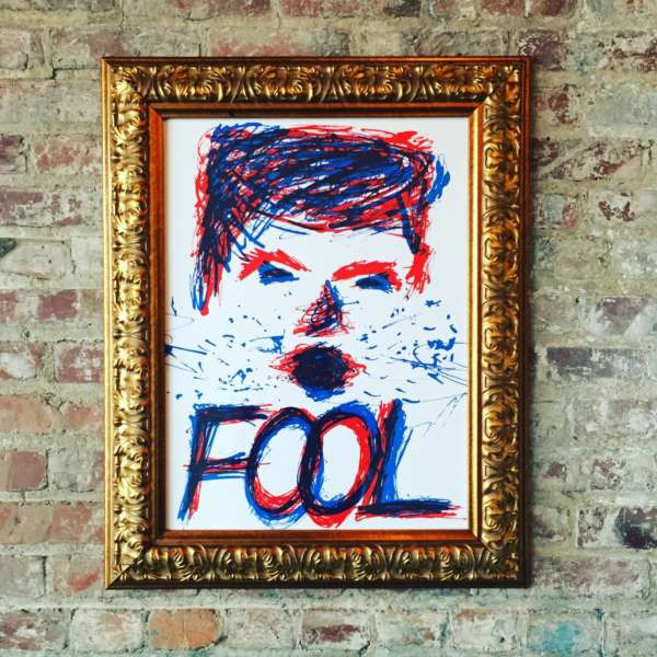"Ink splattered portrait of Donald Trump's face above the word ""Fool"" in gold frame hanging on a brick wall."