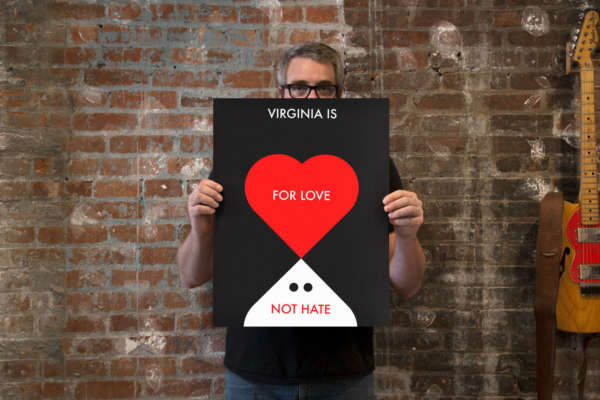 "Studio photo of a designer holding a graphic poster that reads ""Virginia Is For Love Not Hate."""