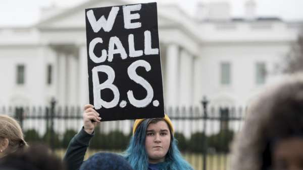 "Photo of a student at a rally holding a sign with large painted black letters that reads ""WE CALL B.S."""