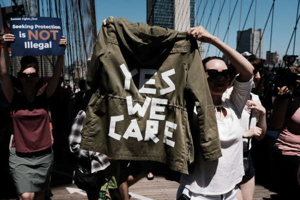 A green jacket with words written in tape 'YES WE CARE' is held up in a protest on a bridge in New York City.